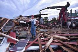 Lars Demander, an eighth-generation farmer at Clover Nook Farm in Bethany is photographed at the remains of  a 250-year-old barn that was destroyed by a tornado. Family friend Bob Carrington dismantles what is left of the barn using his forklift.