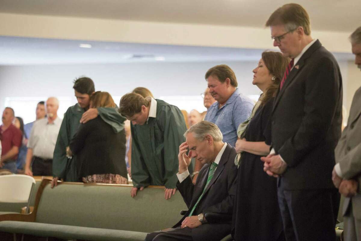 Texas Gov. Greg Abbott, center, and Lt. Gov. Dan Patrick, right, pray with Santa Fe High School graduating seniors, in green robes, at a church service in Santa Fe, Texas, May 20, 2018. A gunman killed 10 people and wounded 13 others at the high school on Friday. (Michael Stravato/The New York Times)