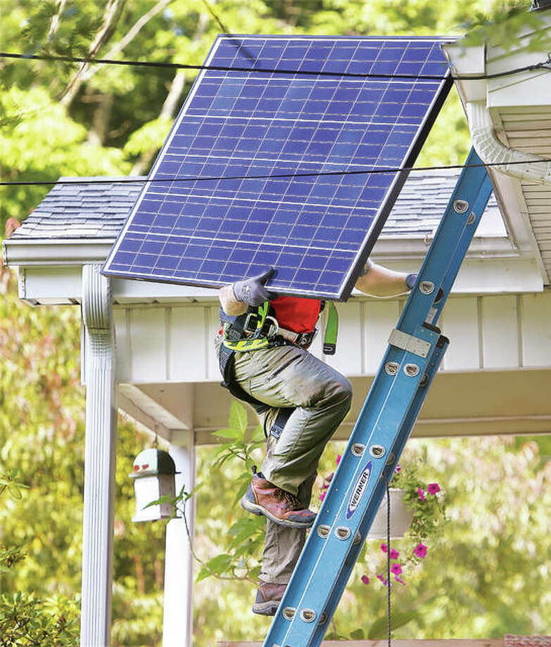 In this 2016 photo, a worker carries a solar panel to the roof of a house in the 500 block of Mulberry Streeet in Godrey.
