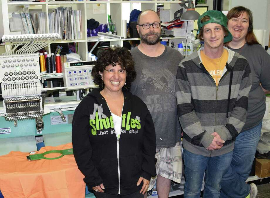 Jill Weiss, left, is the owner of Fat City in New Milford, which specializes in screen printing, embroidery and promotions. She is shown with staff members, Dennis Cieklinski, head printer, Charlie Grubb, graphic designer and assistant printer, and Heather Detrick, manager. Photo: Deborah Rose / Hearst Connecticut Media / The News-Times  / Spectrum