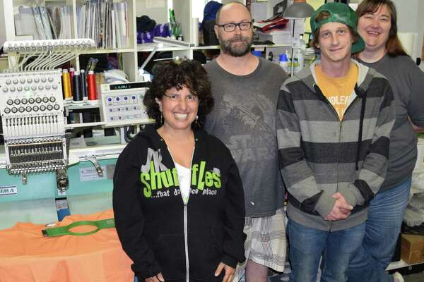 Jill Weiss, left, is the owner of Fat City in New Milford, which specializes in screen printing, embroidery and promotions. She is shown with staff members, Dennis Cieklinski, head printer, Charlie Grubb, graphic designer and assistant printer, and Heather Detrick, manager.