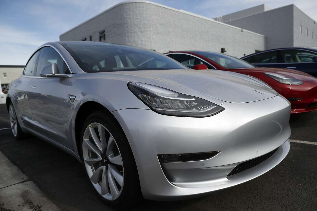 FILE- In this April 15, 2018, file photo unsold 2018 Model 3 Long Range versions sit on a Tesla dealer's lot in the south Denver suburb of Littleton, Colo. Long emergency stopping distances, difficult-to-use controls and a harsh ride stopped Tesla�s Model 3 electric car from getting a recommended buy rating from Consumer Reports. The Model 3 is Tesla�s first attempt to appeal to mass-market buyers. The car that starts at $35,000 but can run as high as $78,000 has been plagued by production delays. (AP Photo/David Zalubowski, File)