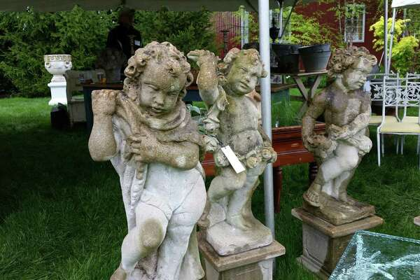 Stone garden cherubs stood outside the tent for Pillars Antiques of Freeport, Maine, one of 60 vendors this year at the 18th annual Trade Secrets Rare Plant and Garden Antiques Sale held at LionRock Farm, a 600-acre farm at 30 Hosier Road in Sharon.