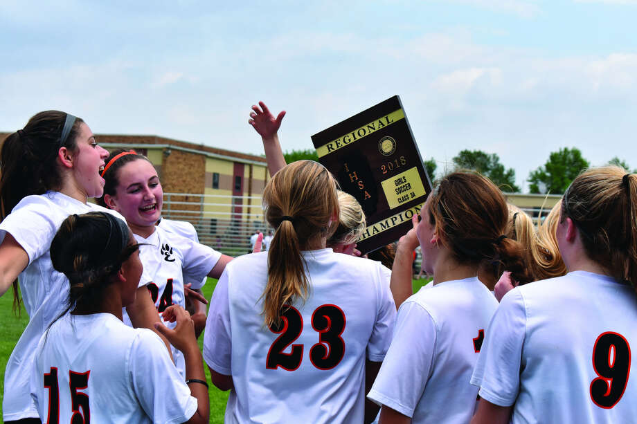 Members of the Edwardsville girls' soccer team celebrate with the Class 3A Granite City Regional championship plaque.