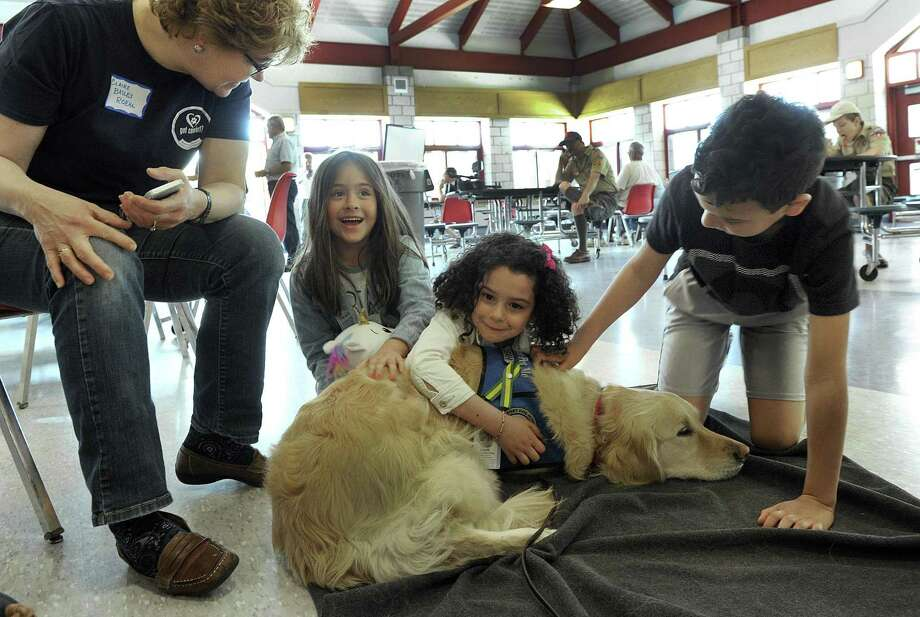 Claire Bailey Roehl, left, of New Fairfield, a volunteer with a dog rescue group linked to Immanuel Lutheran Church in Danbury, introduces Leah to, from left, Isabella Hess, 7, Analia Garcia, 7, and her brother Jhandel, 8. The kids were arriving for lunch at the New Fairfield High School shelter Monday, May 21, 2018. Photo: Carol Kaliff / Hearst Connecticut Media / The News-Times