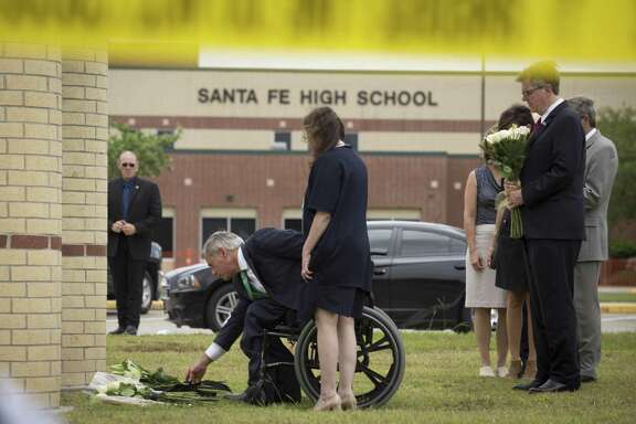 Gov. Greg Abbott, with his wife Cecilia, and Lt. Gov. Dan Patrick, right, place flowers at Santa Fe High School in Santa Fe, Texas, on May 20, 2018. A gunman killed 10 people and wounded 13 others at the high school on Friday.