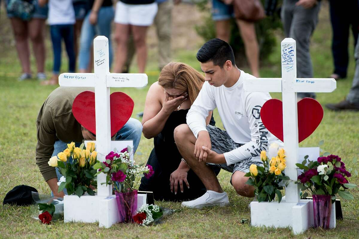 People visit a cross for Christopher Stone at a memorial for the victims of the Santa Fe High School shooting on May 21, 2018 in Santa Fe, Texas. / AFP PHOTO / Brendan SmialowskiBRENDAN SMIALOWSKI/AFP/Getty Images
