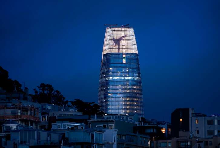 Figures dance across the crown of Salesforce Tower on Thursday, May 17, 2018, in San Francisco, as part of a light installation by artist Jim Campbell.