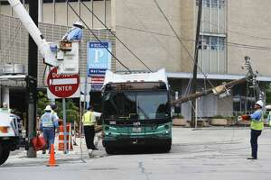 CPS Energy workers move down power lines as emergency personnel remove passengers from a VIA Metropolitan Transit bus trapped by the power lines at the corner of East Quincy Street and Richmond Avenue, Monday, May 21, 2018. They were trapped for over one hour. According to bus passenger Michael Orosco, 55, the bus driver was turning onto Quincy from Main Street and cut the turn too wide clipping a power pole that fell causing the lines to fall over the bus. Around 10 passengers and the driver were trapped inside while workers removes power lines away from the bus. Orosco said the driver told passengers not to worry because the bus was well insulated.