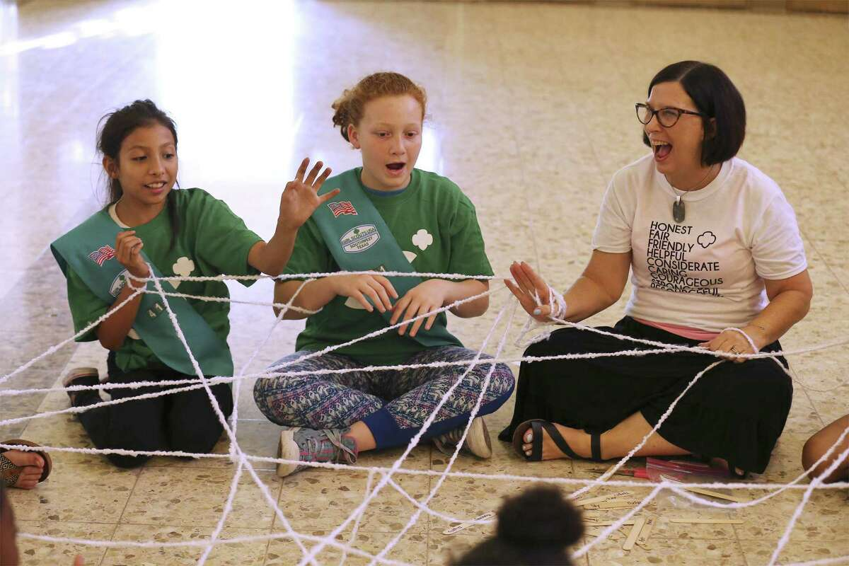 Troop 41 leader Janet Henry (right) laughs while taking part in an activity with a group of girl scouts on Wednesday, May 16, 2018. Girl Scouts of Southwest Texas has awarded Henry with the Honor Pin for helping more than 50 girls in homeless situations find a sense of normalcy through a Girl Scout troop she founded at the SAMMinistries transitional living and learning center. Henry has been a leader for 13 years overseeing a girls troop at the center. Her impact is such that her current co-leader Heather Redding was part of the troop when she was a young woman and now she helps Henry with a new generation of girl scouts. (Kin Man Hui/San Antonio Express-News)