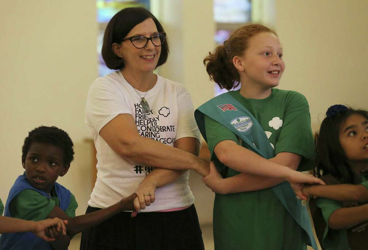 Troop 41 leader Janet Henry joins hands with a group of girl scouts during an activity on Wednesday, May 16, 2018. Girl Scouts of Southwest Texas has awarded Henry with the Honor Pin for helping more than 50 girls in homeless situations find a sense of normalcy through a Girl Scout troop she founded at the SAMMinistries transitional living and learning center. Henry has been a leader for 13 years overseeing a girls troop at the center. Her impact is such that her current co-leader Heather Redding was part of the troop when she was a young woman and now she helps Henry with a new generation of girl scouts. (Kin Man Hui/San Antonio Express-News)