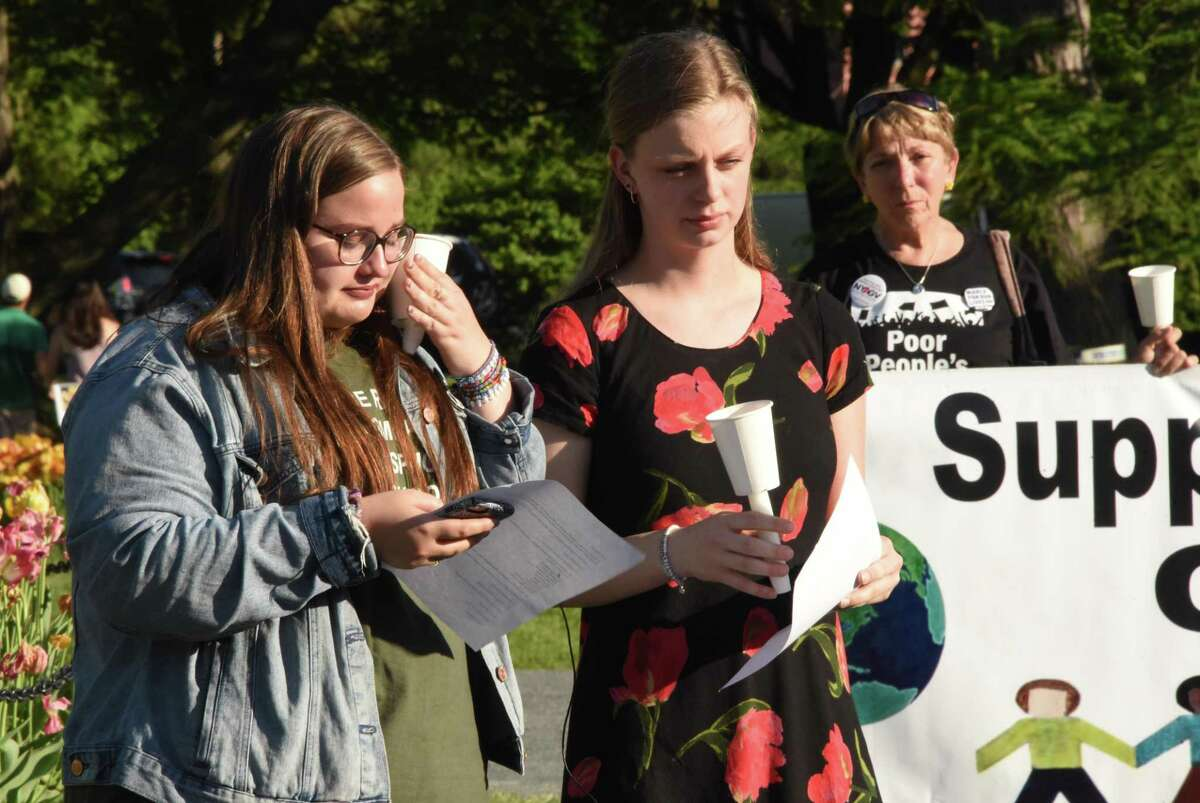 Lydia Martell of Bethlehem High School wipes a tear as she and Lilly Hutton of Columbia High School read the names of Santa Fe victims with a moment of silence following during a candlelight vigil held in Washington Park on Monday, May 21, 2018 in Albany, N.Y. The vigil was organizes by Capital Region students from March for Our Lives to honor the 10 students and teachers gunned down in Santa Fe, Texas (Lori Van Buren/Times Union)