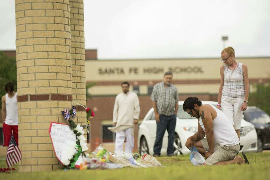 Alex Arriaga pays his respects to the victims of the Santa Fe School shooting on front of the school, Sunday, May 20, 2018, in Santa Fe. ( Marie D. De Jesus / Houston Chronicle ) Photo: Marie D. De Jesus, Houston Chronicle / Houston Chronicle / © 2018 Houston Chronicle