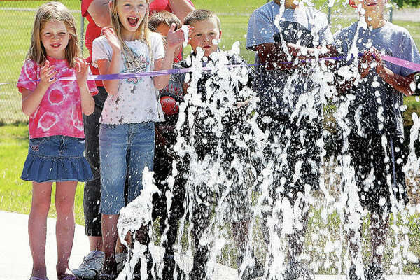 Children delight as water shoots up from the ground at Hartford's Splash Park.