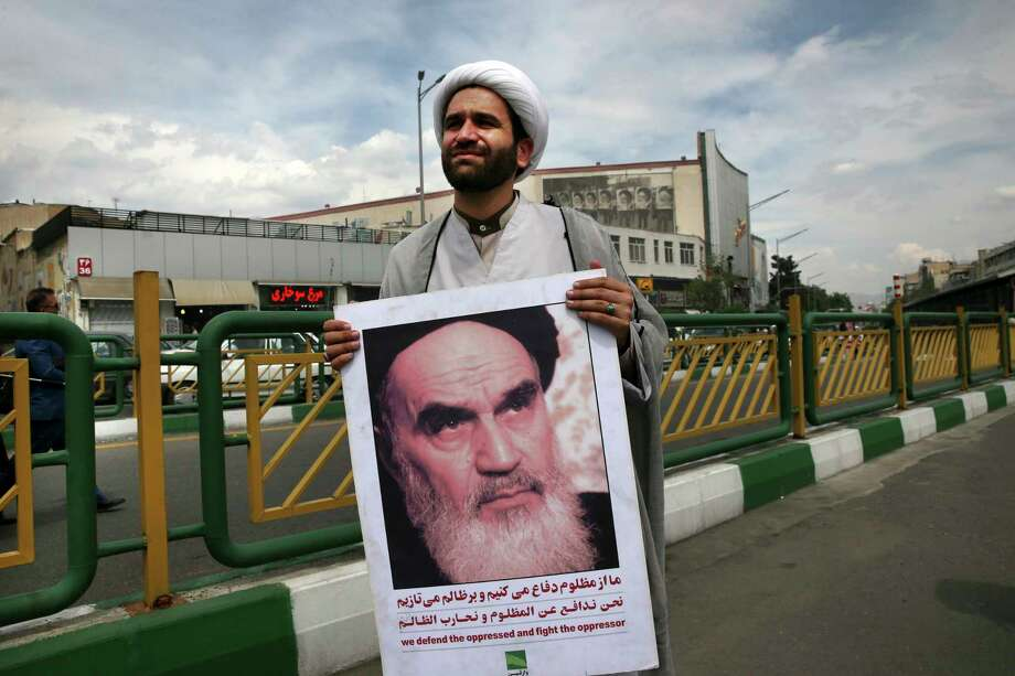 A cleric holds a poster showing portrait of the late Iranian revolutionary founder Ayatollah Khomeini at the conclusion of an anti-U.S. gathering in Tehran, Iran, Friday, May 11, 2018. Thousands of Iranians took to the streets in cities across the country to protest U.S. President Donald Trump's decision to pull out of the nuclear deal with world powers. (AP Photo/Vahid Salemi) Photo: Vahid Salemi / Copyright 2018 The Associated Press. All rights reserved.