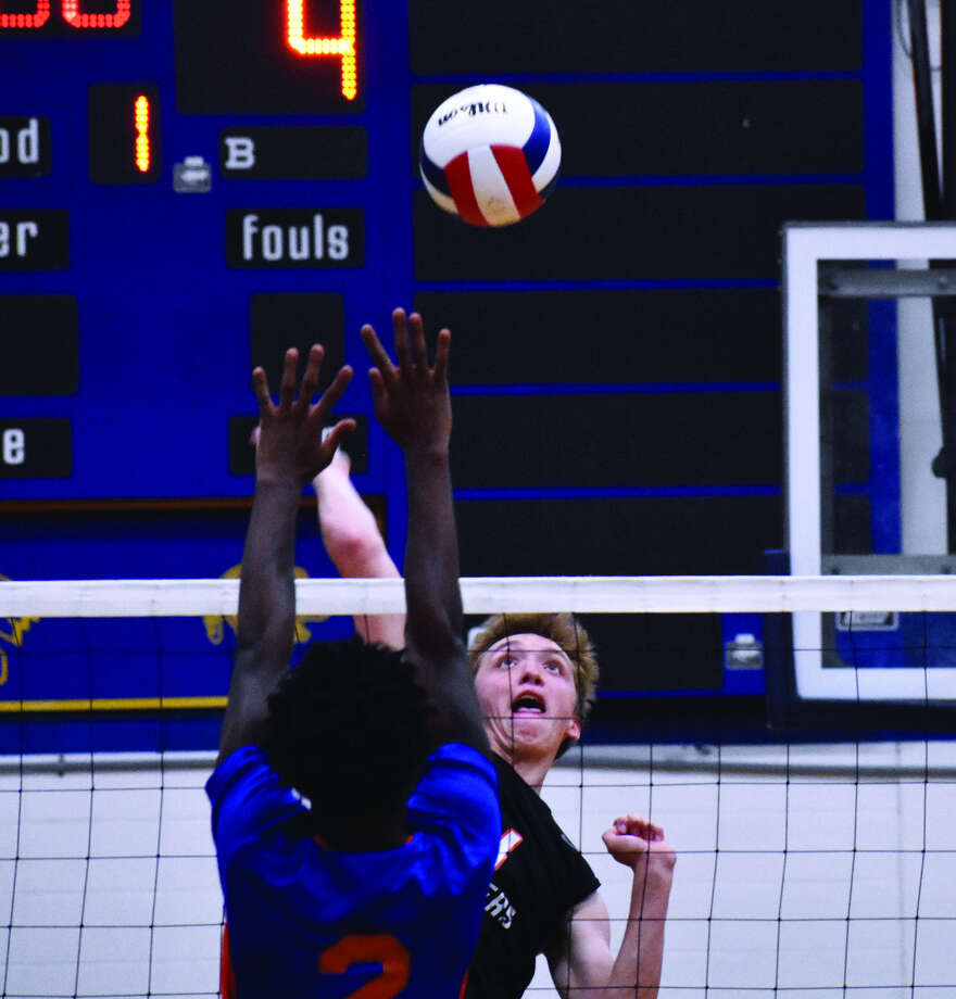 Edwardsville senior Lucas Verdun slams down a kill during the first game against East St. Louis at Belleville Althoff.