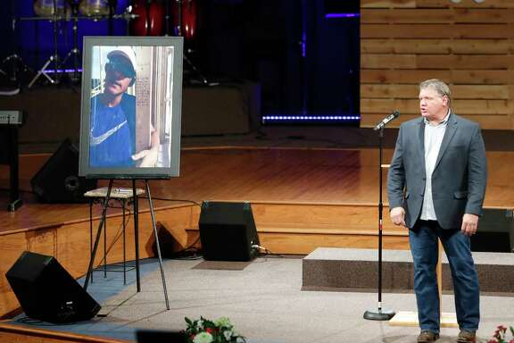 Pastor Keenan Smith stands next to a photo of Christian Riley Garcia, one of the  victims of the Santa Fe High School shooting, on the stage during a prayer service at Crosby Church, Monday, May 21, 2018, in Crosby, Garcia and all of the other students killed, Friday. Garcia grew up in the church in Crosby.