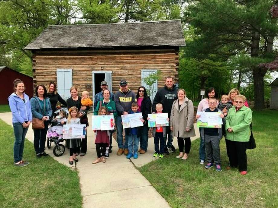 Sanford Centennial Museum's 2018 Log Cabin Art Contest winners and their families posed in front of 'the log cabin' at the museum on May 20. Student winners are pictured (from left to right) Jasmine Jackson, Izzy Messer, Ethan McPheeters, Carter Butzin and Kaleb McLosky. (Courtesy of Karen Sherman Ketover)