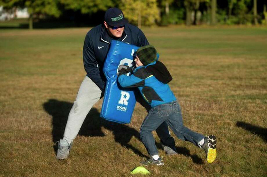 Grant Markel, 7, runs into Northwood University football player Jake Van Ittersum during a football exercise at 'Go MAD' day on Nov. 3, 2017, at Blessed Sacrament School in Midland. (Katy Kildee/kkildee@mdn.net)