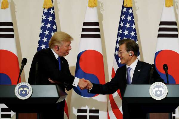 President Donald Trump (left) shakes hands with Moon Jae-in, South Korea's president, during a news conference at the presidential Blue House in Seoul, South Korea, on Nov. 7, 2017.