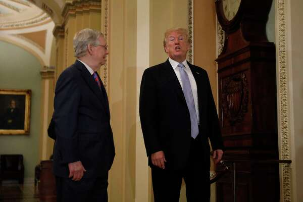 President Donald Trump (right) speaks while walking with Senate Majority Leader Mitch McConnell, R-Ky., on Capitol Hill in Washington on May 15, 2018.