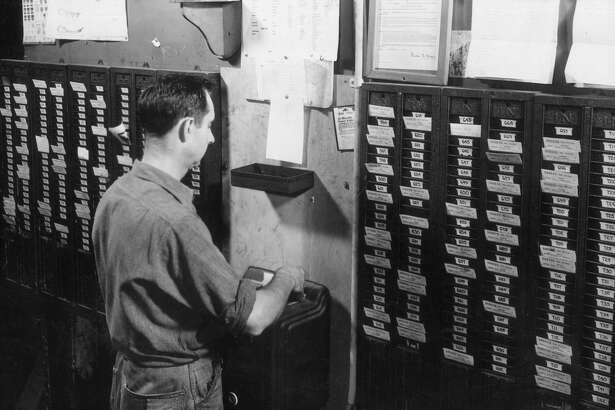 circa 1945:  A male worker inserts his employee time card into a punch clock, with other time cards hanging in files on the wall around him.  (Photo by James W. Welgos/Welgos/Getty Images)