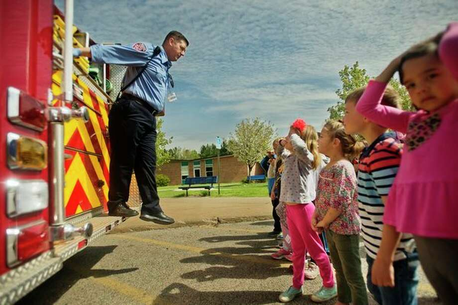 Robert Arnold of the Midland Fire Department gives a tour of the various pieces of equipment on a fire truck to kindergarteners at Adams Elementary on Monday. (Katy Kildee/kkildee@mdn.net)