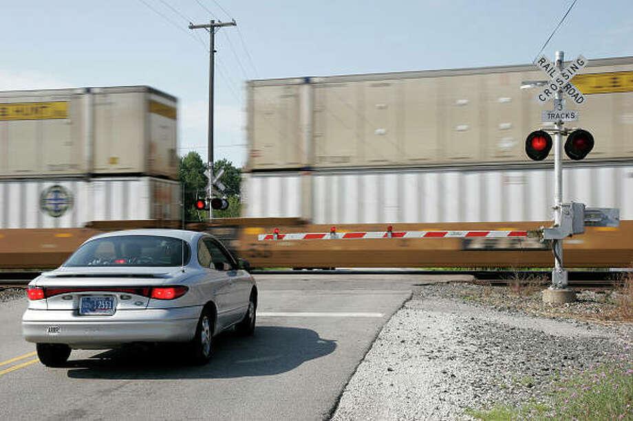 A car waits at a railroad crossing.
