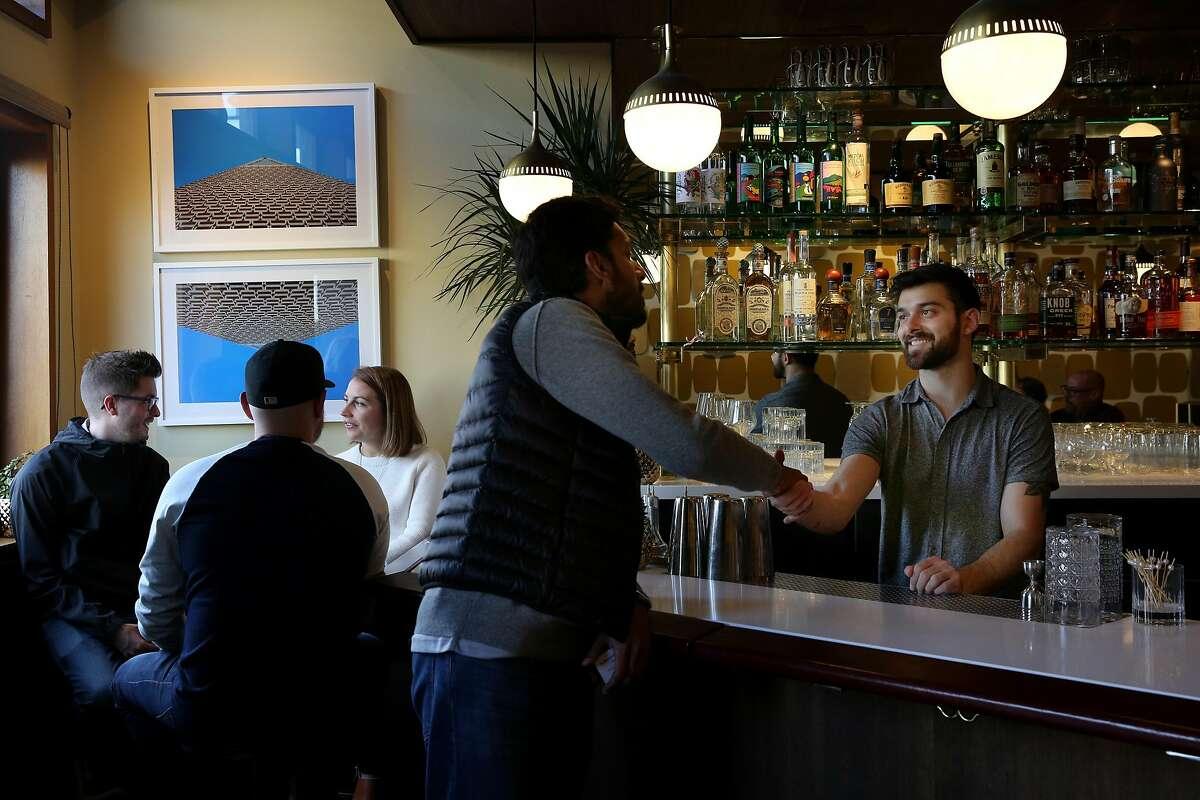 Arjun Venkatesh (center) greets bartender Emilio Salehi at The Beehive, Saturday, May 5, 2018, in San Francisco, Calif. It's located at 842 Valencia Street.