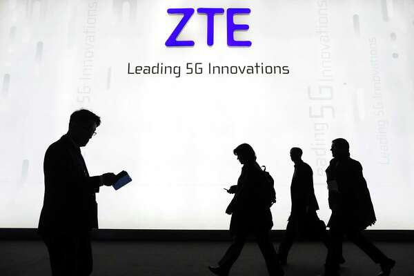 Attendees pass by the ZTE Corp. stand at the Mobile World Congress (MWC) in Barcelona on Feb. 26, 2018.