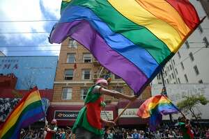 Street performers and Pride supporters walk down Mark Street waving gay pride flags during the Pride Parade in San Francisco, California, on Sunday, June 28, 2015.