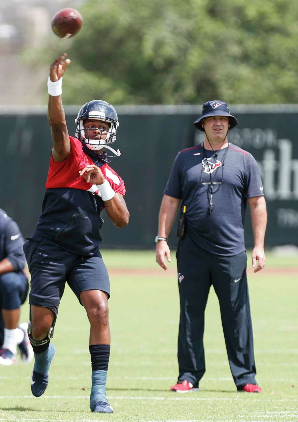 Houston Texans NFL football quarterback Deshaun Watson throws a pass in front of head coach Bill O'Brien during practice in Houston, Tuesday, May 22, 2018. (Brett Coomer/Houston Chronicle via AP)