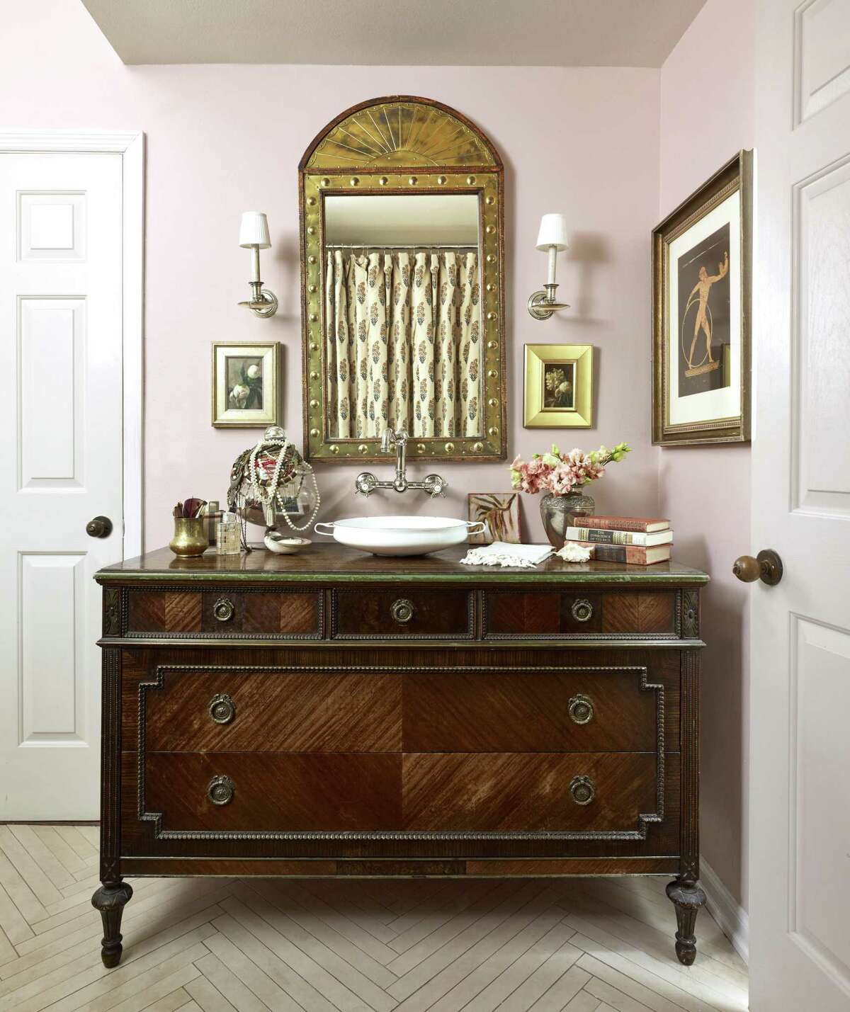 Custom bathroom sink vanities made from antique chests is a growing trend. This one, by Charleston, S.C., designer Alaina Ralphs, has a wild surprise: the shapely sink is actually a paella pan.