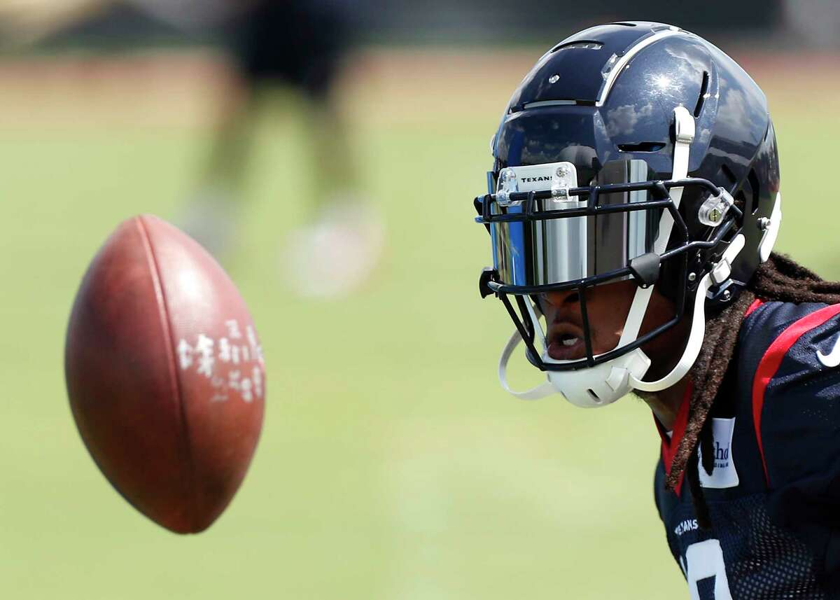Houston Texans wide receiver Deandre Hopkins flips the football back to a coach while running drills during Organized Team Activities at The Methodist Training Center on Tuesday, May 22, 2018, in Houston.
