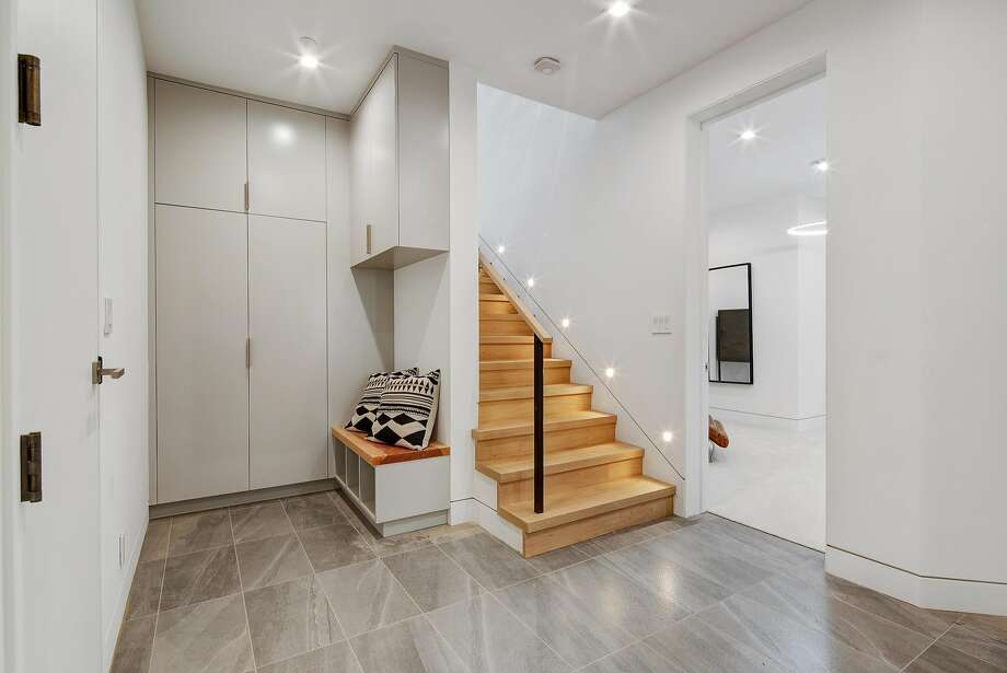 The lower level offers a tile entryway leading to a hardwood staircase. Photo: Circle Visions