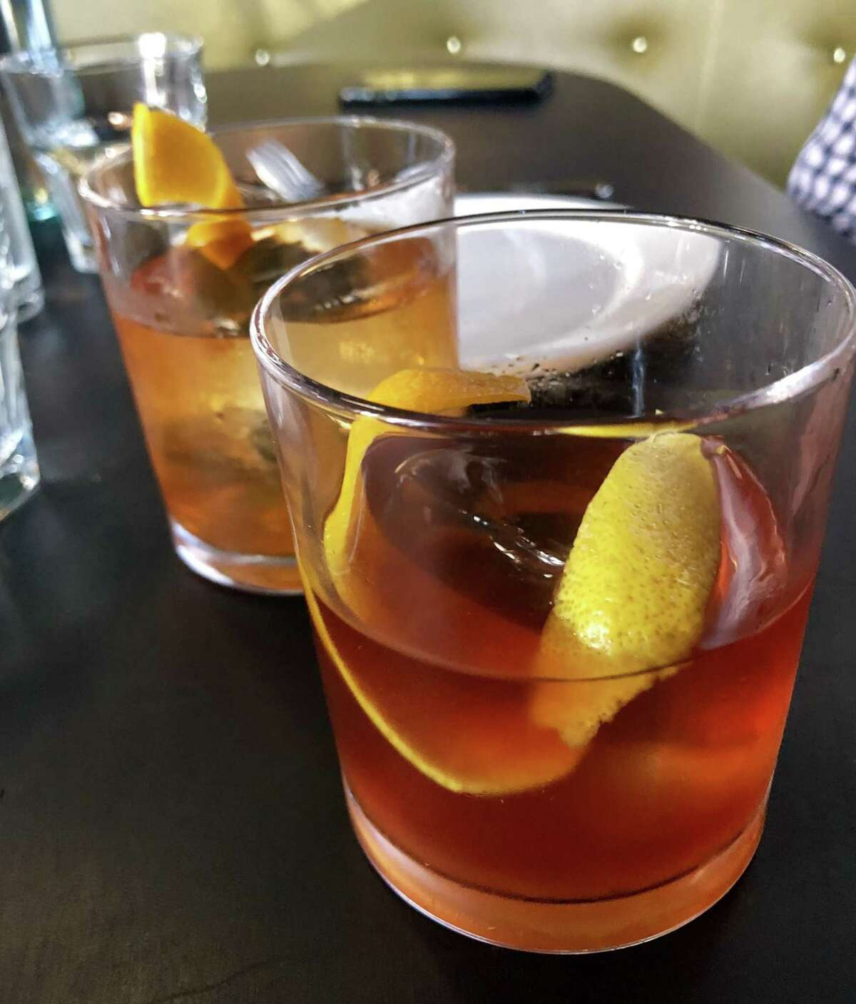 Cocktails, including the manhattan (rear), are well-crafted and spiritous.