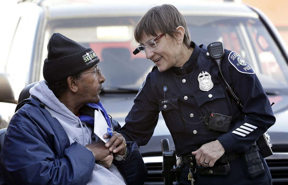 FILE - In this March 12, 2015, file photo, Seattle police officer Debra Pelich, right, wears a video camera on her eyeglasses as she talks with Alex Legesse before a small community gathering in Seattle. While the Seattle Police Department bars officers from using real-time facial recognition in body camera video, privacy activists are concerned that a proliferation of the technology could turn the cameras into tools of mass surveillance. The ACLU and other organizations on Tuesday, May 22, 2018, asked Amazon to stop selling its facial-recognition tool, called Rekognition, to law enforcement agencies. (AP Photo/Elaine Thompson, File)