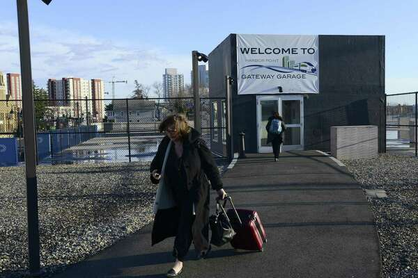 A woman pulls her luggage as she makes her way to the Stamford Train Station after parking at Harbor Point Gateway Garage on April 4, 2018 in Stamford, Connecticut.