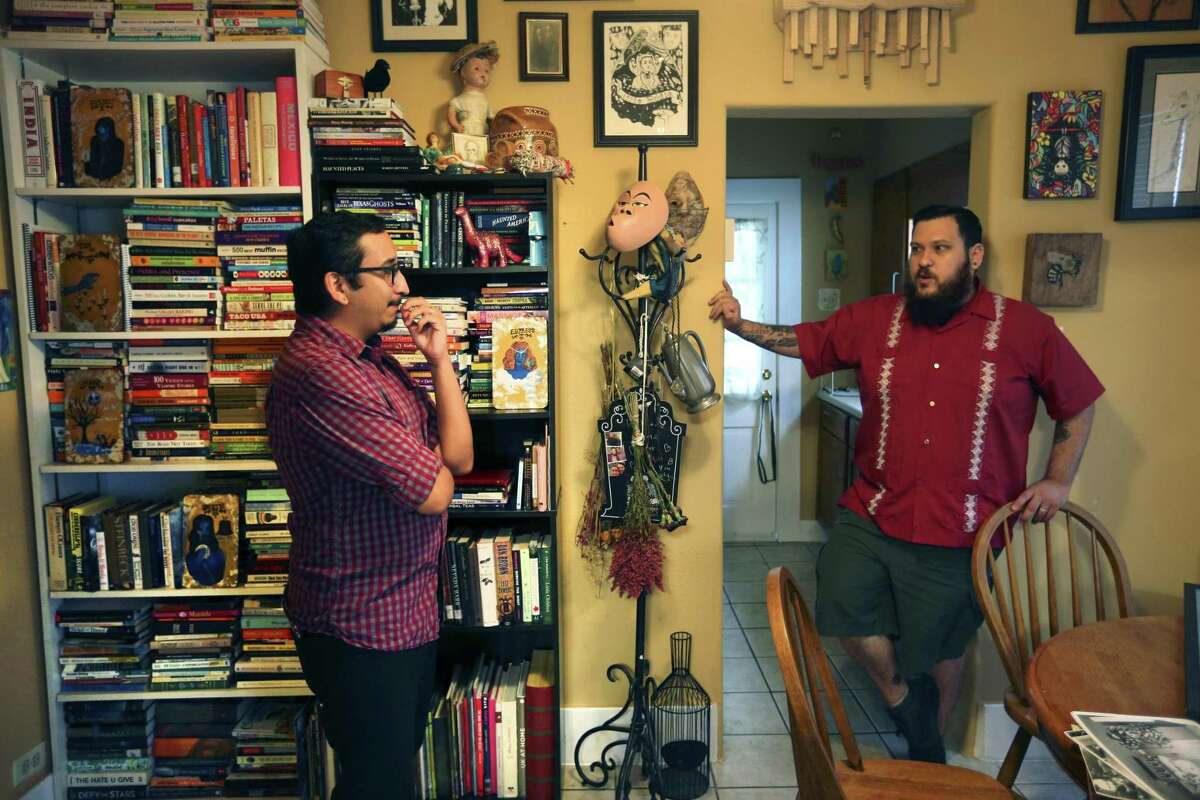 Stephen, left, and Fred Garza-Guzman talk in their home about their paranormal object collection.