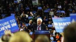 Bernie Sanders speaks to crowds at a rally at Key Arena in Seattle March 20, 2016. He has lately pitching a measure that guarantees a job at a liveable wage to Americans. We can't afford it.