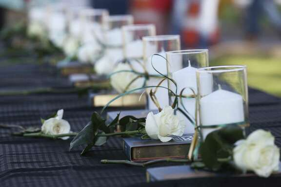 Ten candles, 10 bibles and 10 white roses are representing the 10 deceased in the Santa Fe High School shooting during a candlelight vigil for victims and survivors at Texas First Bank on Friday, May 18, 2018, in Santa Fe.
