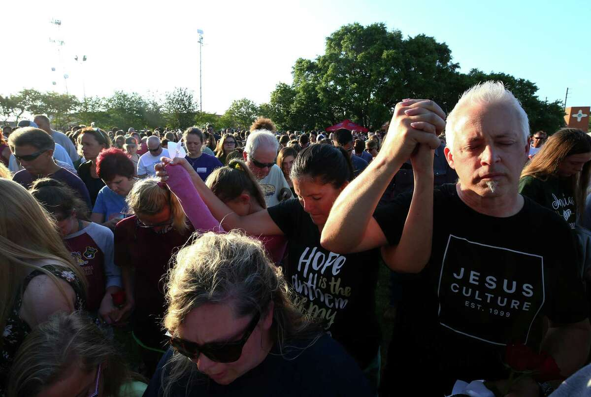 People embrace in prayer behind Texas First Bank during a vigil for the victims of the Santa Fe High School mass shooting Friday, May 18, 2018, in Santa Fe, Texas.
