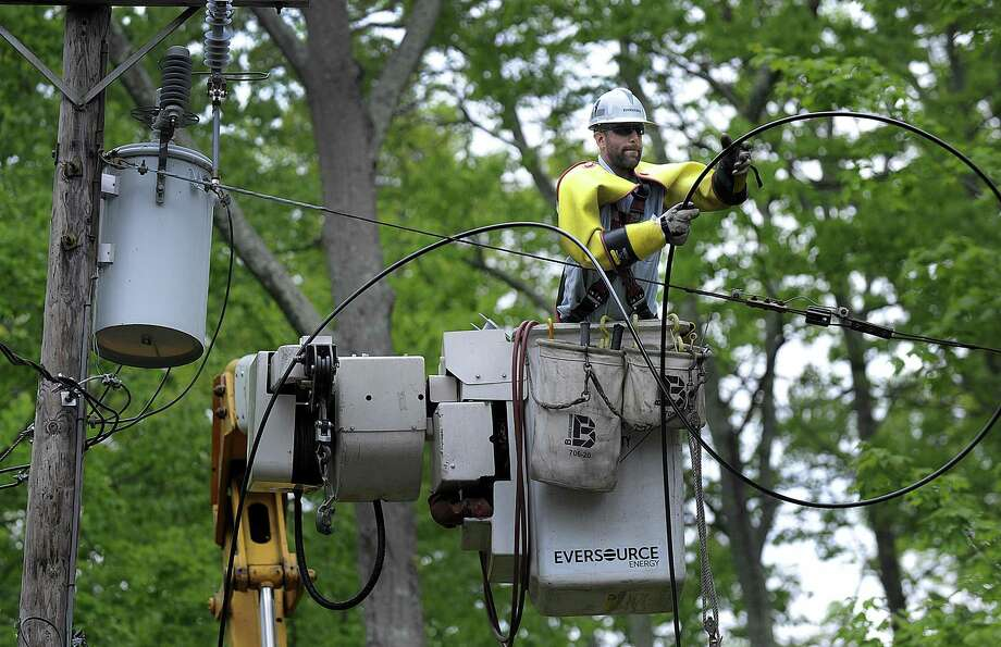 An Eversouce crew from New Hampshire works to restore power on Candlewood Isle in New Fairfield Tuesday, May 22, 2018. It has been one week since a severe storm, classified as a macroburst, came through the area. Photo: Carol Kaliff / Hearst Connecticut Media / The News-Times