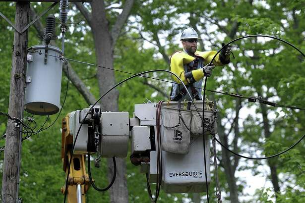 An Eversouce crew from New Hampshire works to restore power on Candlewood Isle in New Fairfield Tuesday, May 22, 2018. It has been one week since a severe storm, classified as a macroburst, came through the area.