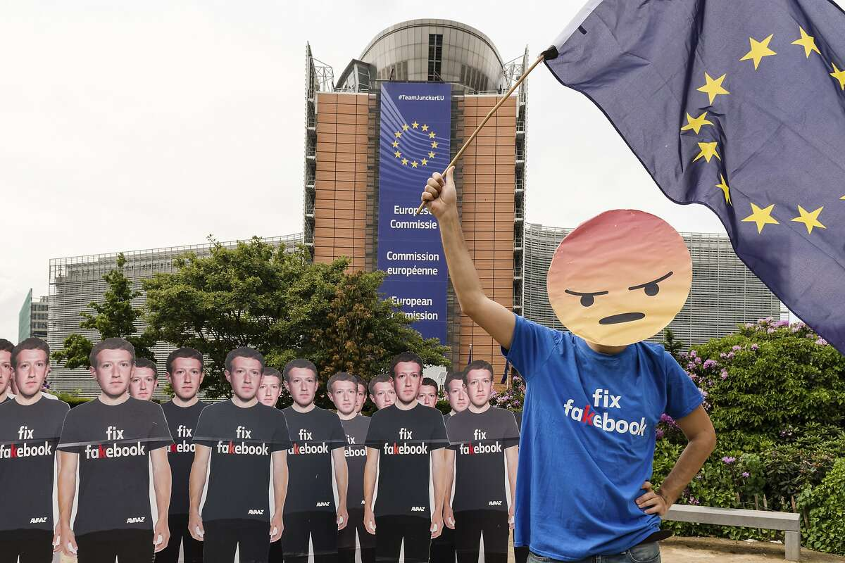 An Avaaz demonstrator waves the European flag as he stands next to life-sized Zuckerberg cutouts to protest against fake Facebook accounts spreading disinformation on the platform, near the EU Commission in Brussels, Tuesday, May 22, 2018. European Union lawmakers plan to press Facebook CEO Mark Zuckerberg on Tuesday about data protection standards at the internet giant at a hearing focused on a scandal over the alleged misuse of the personal information of millions of people. (AP Photo/Geert Vanden Wijngaert)