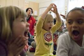 Nova Lucas, 4, Elodie Semancik-Howe, 5 (yellow shirt in middle), and Elisa Gibson, 5, sing in different languages at the Holy Family Day Home on Tuesday, Feb. 27, 2018 in San Francisco, CA.  If the child care ballot measure passes, it would help families pay tuition at centers like this one.