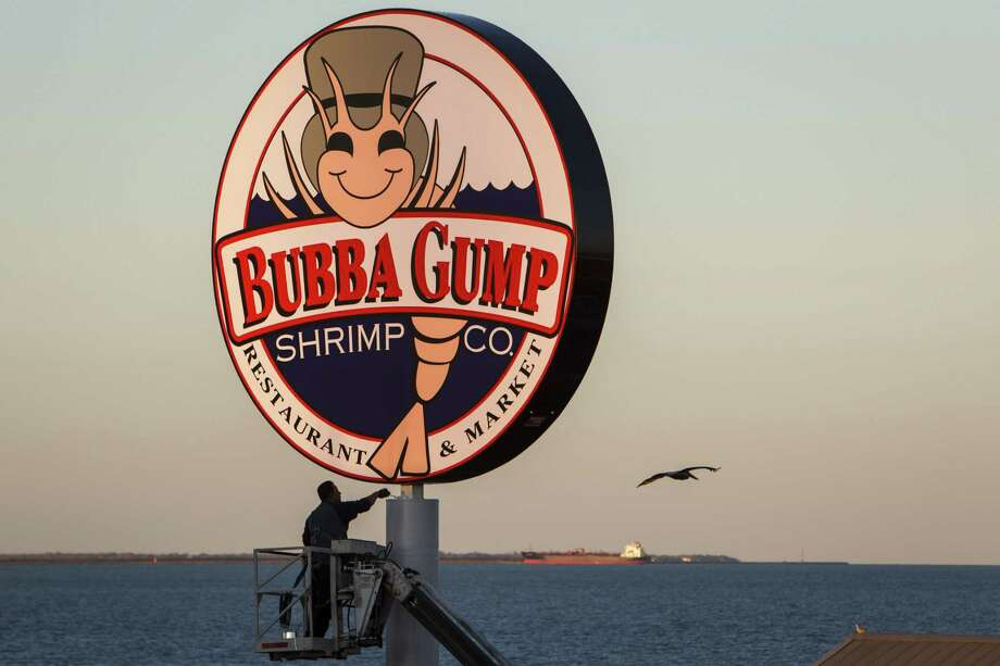 FILE - Gilbert Lopez puts a fresh coat of paint on the Bubba Gump Shrimp Co. pole outside the Kemah Boardwalk restaurant on Feb. 13, 2013, in Kemah. JP Morgan Chase Bank is suing Landry's, the Houston-based hospitality company, for $20 million over costs related to its 2015 credit card data breach. Photo: Michael Paulsen, Staff / Houston Chronicle / © 2013 Houston Chronicle