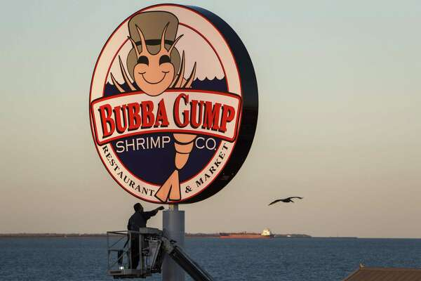Gilbert Lopez puts a fresh coat of paint on the Bubba Gump Shrimp Co. pole outside the Kemah Boardwalk restaurant, Wednesday, Feb. 13, 2013, in Kemah.  The restaurant, which was previously Joe's Crab Shack, is expected to open this weekend.  ( Michael Paulsen / Houston Chronicle )