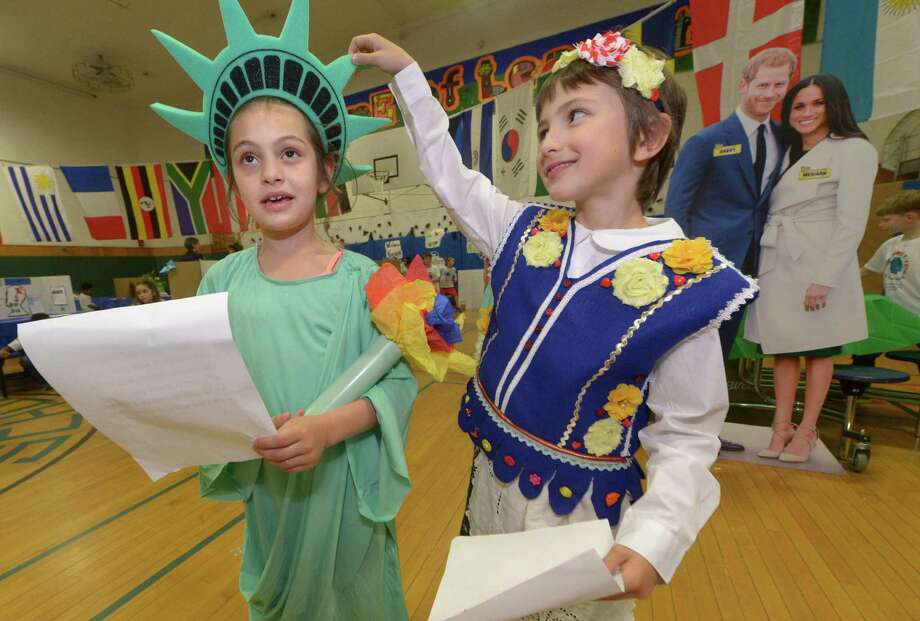 Amelia Rosenberg represents America and New York and Raven Bagnatti represents Poland as they prepare to give a welcome speech to the fifth grade during the 12th annual second grade All Around the World Culture Fair at Columbus Magnet School Tuesday, May 22, 2018, in Norwalk, Conn. Every year, Columbus second graders present personal research on their cultural backgrounds. Photo: Erik Trautmann / Hearst Connecticut Media / Norwalk Hour