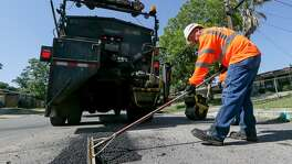 Jesse Cisneros with the city's Transportation and Capital Improvements (TCI)  levels hot asphalt with a rake before rolling it while reapiring a pothole on Yolanda St. on the city's West Side on Wednesday, May 16, 2018.  MARVIN PFEIFFER/mpfeiffer@express-news.net